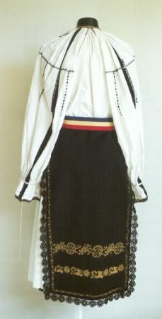 Romanian Women's costume from county of Sibiu  Black front and back aprons (catrinţe) made of a single width of black felted woollen material. These are decorated with two rows of motifs worked in gold thread, and with crochet black lace on the sides and the front apron has a fringe made of black silk thread on the hem. Pleated white cotton underskirt (poale) Narrow fabric belt (brâu) made of ribbon in the colours of the Romanian flag