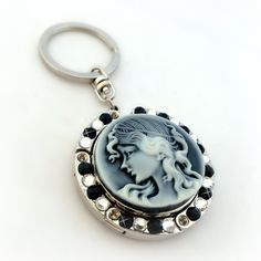 Black lady cameo keychain, folding purse hook, bag charm. A lovely accessory that is also a great gift idea, this black lady cameo keychain has many uses. Decorated with crystals it is also a folding purse hook and it can also be used as a bag charm. A versatile accessory that you can use to hang your purse or your keys or just as a bag charm to decorate your bag. It is also a great gift idea for ladies who love elegant accessories. Available in three colours, black, purple or red. Just...