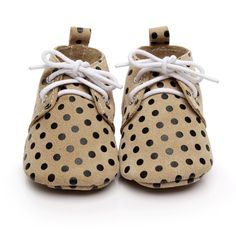 Children's genuine leather suede oxfords in tan with black spots. Featuring white laces and pull tab for ease of wear. Soft suede sole allows for natural foot movement, essential for foot health and natural development in little bebes.   #kidsshoes #girlshoes #babyshoes #babyfashion #kidfashion #printedshoes #polkadots