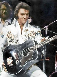 Elvis performing at the Aloha from Hawaii concert with the Gibson Ebony Dove guitar his father bought for him.