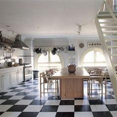 Cuisine-salle à manger avec grande table centrale en bois, chaises Thonet et Kokki, plan de travail en terrazzo