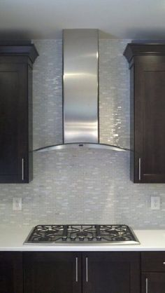 Stainless range hood and glass tile backsplash. Kitchen  #interior design by SKD Studios skdstudios.com