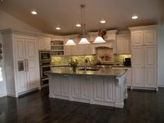 Here is a beautiful kitchen that The Cabinet Gallery had the pleasure of designing and manufacturing.  The layout of the original kitchen was very small and awkward.  The new cabinets are made of maple and painted white with a custom green glaze made especially for this kitchen to accent the granite countertops and tile backsplash.
