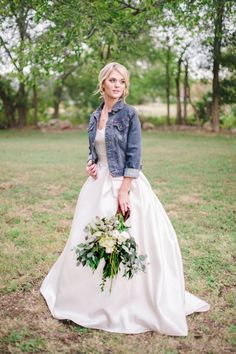 blue denim jacket with rolle dup sleeves over a modern wedding ball gown