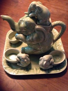 A wonderful Elephant themed tea service. Teapot is a mother elephant with a baby elephant perched on her back as the lid. There are 4 cups that