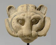AN ETRUSCAN TERRACOTTA ANTEFIX   CIRCA 6TH CENTURY B.C.   Molded in the form of a panther head, with rounded ears and large bulging eyes, two protruding knobs above, the mane a flange encircling the jowls, the long nose merging with the exaggerated muzzle, painted with black and red details including eyelashes, the arching tile projecting from the back of the head  9½ in. (24.1 cm.) high