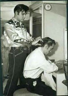 Elvis helping Johnny Cash with his hair.