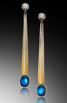 A modern earring design by Adam Neeley.  Egyptian Moonstone Earrings are elegant and exotic. In this unique earring design, sumptuous rainbow moonstones are suspended by lines of gradient spectra gold, with classic diamonds at the ear.