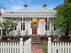 Corrugated iron victorian house exterior with picket fence landscaped garden