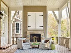 Thoughtful touches such as the branch railing make spaces like the rear porch a stand-out. Dixon also designed a handsome pair of shutters from shiplap boards and iron strap hinges to conceal an outdoor television. Swivel chairs from Lane Venture, along with a bold rug from Myers Carpet, provide all the comforts of an indoor room.
