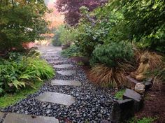 Polished Black River Rock With Stone Walkway and Small Plants and Big Trees With Buddha Statue and Poth With Stone Border