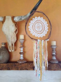 Hand made wooden frame dreamcatcher with a lace doily center and hanging fabric material.  Diameter: Approx: 12 inches Hanging: Approx: 34 inches