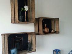 Fruitkistjes/appelkistjes aan de muur. Blauwe achterwand en blauw/koper accesoires.