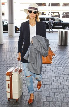 Jessica Alba looks perfectly polished while traveling in a brimmed fedora, navy jacket and ripped jeans