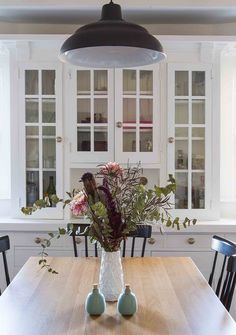 Folken brought light to the dining room by painting the old built-in and wooden wall panels white, adding farmhouse pendant lights over the table, new hardware to the cabinetry, and of course, a fresh bouquet of flowers to put the finishing touches on the bright new space.