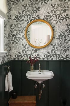 The relocated powder room, with Oakleaf wallpaper by Marthe Armitage from Hamilton Weston. The couple had it custom-printed in an olive green to match the wainscoting, which is painted in Portola's Troubadour.