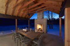 Douglas fir columns frame views from the porch, located just adjacent to the living, dining, and kitchen space. A sandstone fireplace bookends this space, creating a sheltering and warming effect. Photo 4 of Off-Grid Retreat modern home Contemporary Wood Burning Stoves, Sandstone Fireplace, Building A Cabin, Indoor Outdoor, Outdoor Dining, Dining Area, Outdoor Life, Outdoor Rooms, Rustic Design