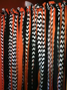 Halloween Backdrop for Halloween Party  Used 2 Yards of each fabric, cut up in 2-3 inch widths.   Used a spring rod from walmart and tide each piece of fabric on it  Total spent on this fun easy photo prop was 23 dollars!