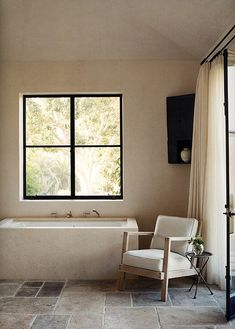 tile flooring. comfy chair. stone bathtub. Found at Rustic Bathrooms on The Style Files.