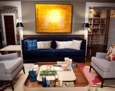 "Carrie and Big's living room includes a sofa by Montauk Sofa upholstered in blue wool-mohair from Donghia and a pair of beige midcentury side chairs. The bright floral Birdie Blossom Cushion by Paul Smith for the Rug Company adds a classic ""Carrie"" touch."