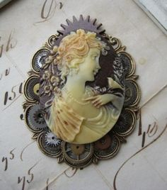 A clever setting of tiny antique gears and wheels distinguishes  Violette Noble's Steampunk Cameo Brooch. From making-jewelry-now.com