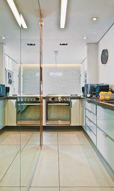 A cozinha deste apartamento mede só 7 m², mas não falta espaço nem conforto para o morador preparar seus quitutes. Enquanto o espelho em frente à pia traz amplitude, os spots embutidos no forro clareiam a área da bancada por completo – a distância entre eles é de 1,20 m. As lâmpadas halógenas PAR 20 de 50 w têm uma coloração amarelada, que se contrapõe à luz fria das fluorescentes T5 de 28 w, no centro do ambiente. Essas opções contam com um difusor acrílico capaz de atenuar reflexos e…