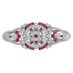 Platinum, Diamond and Ruby Brooch   The openwork modified shield motif set throughout with 74 round and 10 marquise-shaped diamonds approximately 5.60 cts., accented by 35 square-cut rubies approximately 4.90 cts., circa 1935, approximately 20.2 dwt.