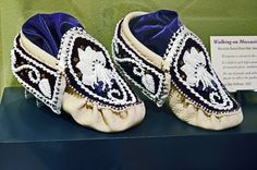 These moccasins are made of Wisconsin-raised Bison hide, velvet, Czech glass beads, and amethyst.  The use of purple and white in these burial moccasins is meant to reflect the quahog shell, the source of wampum.  Made in 2007, these moccasins are part of the Sisters in Spirits: Native American Stories in Rocks and Beads exhibit.