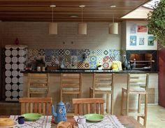 Por aqui, nada de integração com a sala – a cozinha cresceu para os fundos da casa e se converteu em uma área de convivência com direito a ilha e churrasqueira