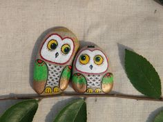 Two owls painted on stones, sitting on a branch
