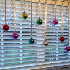Decorate windows with cheap Christmas balls & ribbon.