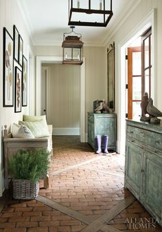 Atlanta Homes Magazine mudroom with plank walls, brick floor, french doors and lanterns