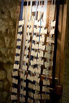 Plan de table avec des petites cartes montées sur de grands rubans.
