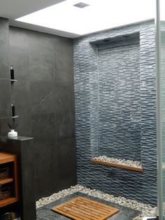 Bali Inspired Bathroom. The bathroom includes an 8ft skylight, waterfall, rain head shower, river rock, hidden shower drain, limestone, teak finishes, wall mounted toilet