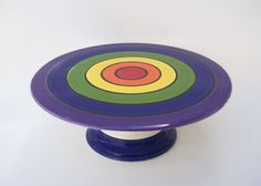 Delight your guests with this cheerful rainbow cake stand full of treats!  This stand is hand painted ceramic, with a bright rainbow colored top.  All stands finished with food-safe glaze. Measures 10 Dia. x 3 1/2 H.  MADE IN NEW MEXICO - USA ★ ALL CONTRIBUTED CONTENT COPYRIGHT © The Heads Creation