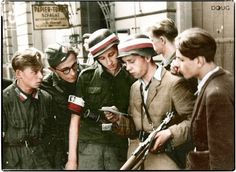 "Members of the 'Kompania Koszta' stand on the corner of Sienkiewicz and Marszalkowska, reading a leaflet from the German General von dem Bach calling for the surrender of all 'Insurgents' during the Polish uprising in Warsaw during August 1944.  (l.) Jerzy Chyliński ""Karol"", Tadeusz Suliński ""Radwan"" (in glasses), Andrzej Główczewski ""Marek"", Wacław Krupiński ""Belina"" and Janusz Chyliński ""Janusz""."