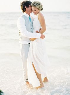 groom in gray vest hugs bride at beach wedding