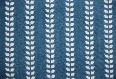 Blue fabric with resist lines of leaves.    The original is a lining in a small stiff silk bonnet, a characteristic part of Swedish peasant woman's costume, dated to the first half of the 19th century. The fabric is a resist-printed fine cotton with white leaves on indigo blue ground. These small patterned fabrics are characteristic for the beginning of the 19th century. They were used mainly for clothing as aprons, kerchiefs and linings.