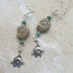 These gorgeous boho fish and shell earrings are on silver plated hypoallergenic ear wires with silver fish charm and manufactured glass bead crystal.