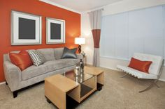 would not have chose orange but it show the versatility of grey Greige sofa against orange wall