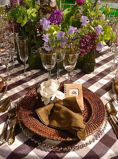 Gorgeous summer table with glass chargers, wicker, gingham, and fresh flowers.