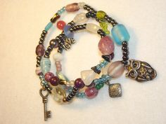 This wrap showcases Glass and Pewter seed beads, Jasper, Hematite and Glass accent beads. Adorned with a key, owl and pewter drop charm.