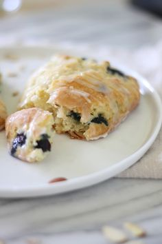 Blue Berry & Almond Scone 2 1/2 cups all purpose flour 1/2 cup granulated sugar 1 tablespoon baking powder 1/2 teaspoon baking soda 1/2 teaspoon salt 1/2 cup cold butter, cut into small chunks 1 cup milk 1 teaspoon vanilla 3/4 cup fresh blueberries 1/3 cup toasted slivered almonds  for the glaze- 1 cup powdered sugar 1/4 teaspoon almond extract 2 teaspoons milk