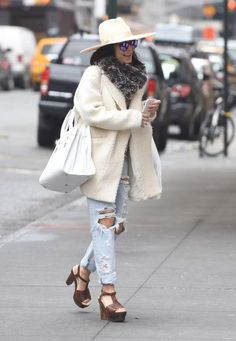 Vanessa Hudgens in ripped boyfriend jeans, heels, an off-white coat and hat in NYC
