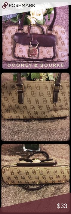 Dooney & Bourke Leather and DB fabric Handbag Classy Dooney and Bourne with gold trim. This is in softly worn condition with little wear on the saddle type leather and gold front trim. Beautiful bag that adds class to any attire! Enjoy this great Handbag at a fabulous price! Dooney & Bourke Bags