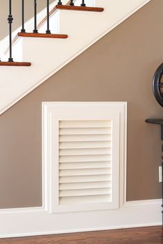 up-grade your cold air vent to a Louvered one . much more attractive than that cheap tin thing!- now they should paint it the same colour as the walls including the trim so it fades away, instead of accentuating it !
