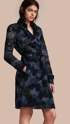 A Burberry trench coat made from crisp Italian macramé lace in a tonal floral design, in ink blue. The silhouette is unlined for a light, airy feel. Showcase the intricate pattern with sleeveless silk or contrast it with a simple tee and denim.