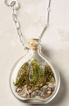 Terrarium Necklace     This blown-glass terrarium pendant captures a unique world-within-a-world in shades of moss, pale pink and sandy grey, adding a touch of the natural to any outfit.