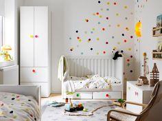 Ein kleines Kinderzimmer u. a. mit STUVA Kleiderschrank mit 2 Türen und 2 Schubladen in Weiß, einem Babybett, das zum Kinderbett umgebaut ist, und einer Banktruhe.