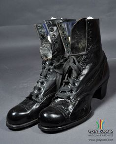 """A pair of ladies', high-topped, black patent leather, """"Banner"""" shoes. They feature a low, chunky heel and have a ribbon-style lace. Grey Roots Museum & Archives Collection."""